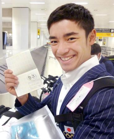 パスポートに押された大会エンブレムのスタンプに笑顔の体操男子日本代表の白井健三=21日、サンパウロ(共同)
