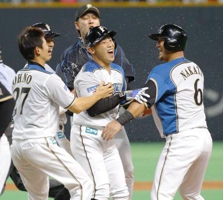 9回、サヨナラの押し出し死球を受けた矢野(中央)と、喜ぶ中田(右端)ら日本ハムナイン=札幌ドーム