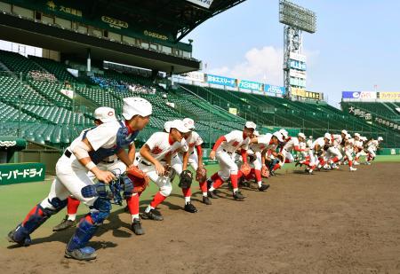 全国高校野球選手権大会の甲子園練習が始まり、グラウンドへ駆けだす智弁学園の選手たち=甲子園