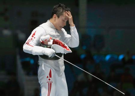 男子フルーレ個人 初戦の2回戦で敗退し、頭を抱える太田雄貴=リオデジャネイロ(共同)