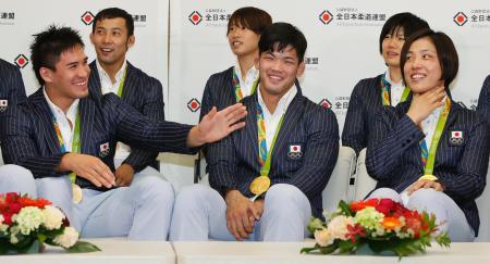 記者会見で笑顔を見せる(前列左から)ベイカー茉秋選手、大野将平選手、田知本遥選手=15日午後、成田空港