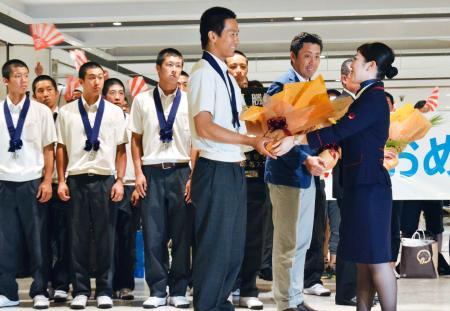 新千歳空港に到着し、花束を受け取る北海高校の大西健斗主将(手前左)=22日午後