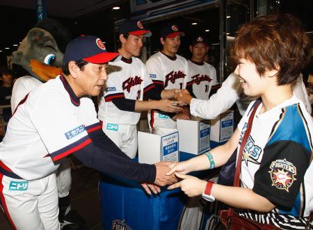 台風10号の被災者支援の募金活動で、ファンと握手する栗山監督(左端)と日本ハムナイン=7日、札幌ドーム