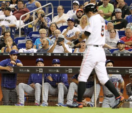 5回、ベンチで試合を見守るドジャース・前田(左から2人目)と、代打で死球を受けたマーリンズのイチロー=マイアミ(共同)