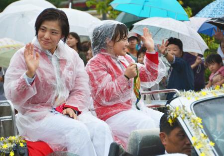 凱旋パレードで、集まった市民に手を振る田知本遥選手(手前)と登坂絵莉選手=12日午後、富山市