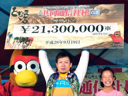 第32回共同通信社杯で優勝し、賞金ボードを掲げる竹内雄作=富山競輪場