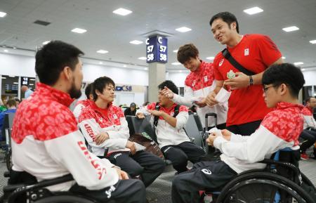 帰国便の搭乗前、空港で談笑する日本選手団の藤本主将(右から2人目)ら=20日、リオデジャネイロ