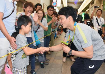 凱旋パレードで子どもと握手するリオ五輪体操男子団体総合金メダリストの田中佑典選手=24日午前、和歌山市