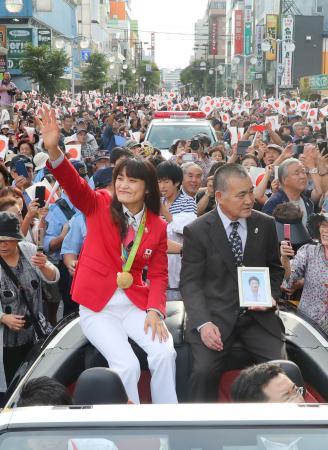 リオ五輪で史上初の女子個人種目4連覇を果たし、国民栄誉賞受賞が決まったレスリングの伊調馨選手(手前左)。出身地の青森県八戸市で行われたパレードで観衆に向かい笑顔で手を振った。隣は母の遺影を持つ父春行さん=24日午後