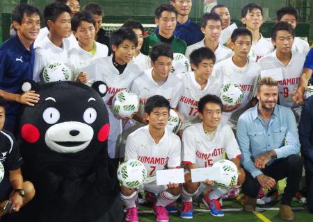 熊本地震の被災地支援イベントで、サッカーの熊本県U―16選抜の選手らと記念写真に納まるデービッド・ベッカム氏(前列右端)=29日、東京都内