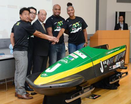 ジャマイカ・ボブスレー連盟向けに開発した新型機「下町スペシャル」の完成品と記念撮影する関係者=5日午前、東京都大田区