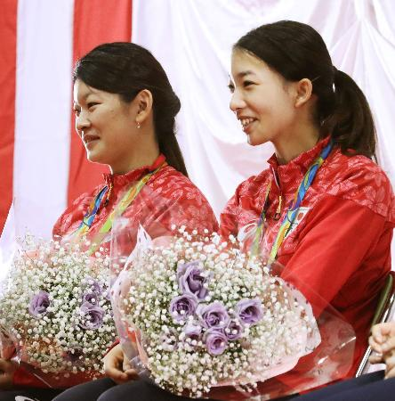 母校の聖ウルスラ学院での祝勝会で、花束を手に笑顔の高橋礼華選手(左)と松友美佐紀選手=5日午前、仙台市