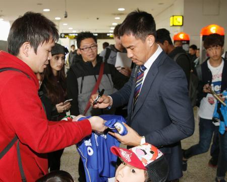 オーストラリア戦が行われるメルボルンに到着し、サインするサッカー日本代表の岡崎(右)=8日(共同)