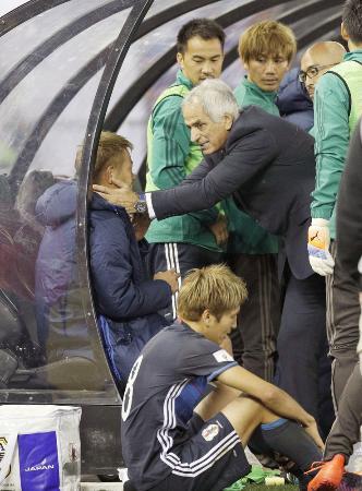 試合後、本田(左)に声を掛けるハリルホジッチ監督。下は原口=メルボルン(共同)