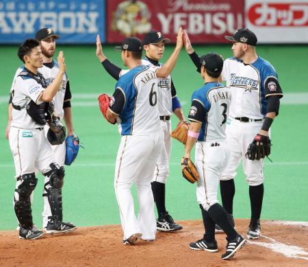 ソフトバンクに勝利し、日本シリーズ進出に王手をかけ、タッチを交わすレアード(右端)ら日本ハムナイン=札幌ドーム