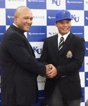 DeNAがドラフト1位指名した浜口遥大投手(右)と握手を交わすラミレス監督=21日午前、横浜市の神奈川大