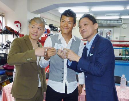 日本ボクシングコミッションから発行されたライセンスを手にする亀田和毅(中央)。左は兄の興毅氏、右は協栄ジムの金平桂一郎会長=27日、東京都新宿区の同ジム