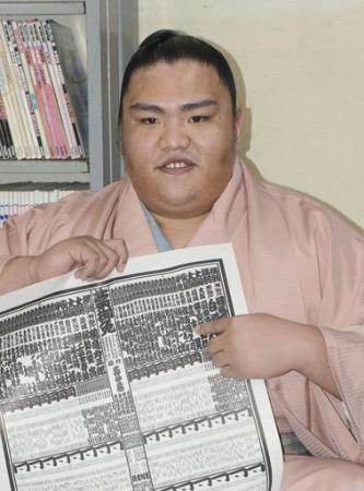 大相撲九州場所の番付表を手にする新小結の御嶽海=10月31日、福岡県新宮町の出羽海部屋宿舎