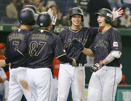 オランダ戦の10回、タイブレークで勝ち越しの満塁本塁打を放ち、山田(右から2人目)らの出迎えを受ける鈴木(右端)=東京ドーム