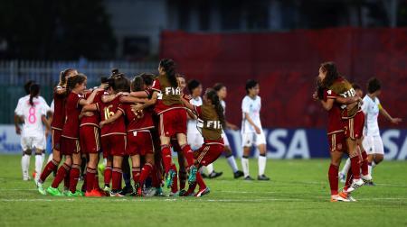 勝利を喜ぶスペインチーム(手前)とピッチを去る日本の選手たち=16日、ポートモレスビー(ゲッティ=共同)