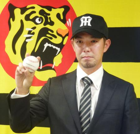 阪神に入団が決まり、ポーズをとる柳瀬明宏投手=18日、兵庫県西宮市の球団事務所