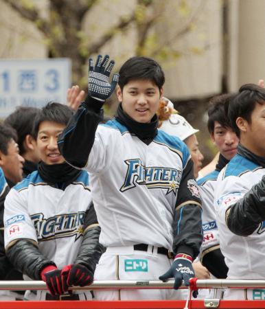 優勝パレードに集まった沿道のファンに手を振る日本ハム・大谷翔平選手=20日午前、札幌市