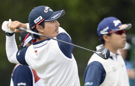第3ラウンド、12番で第2打を放つ石川遼。右は松山英樹=キングストンヒースGC(共同)
