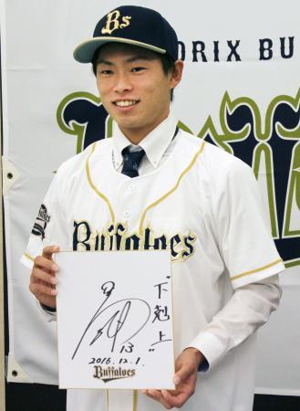 オリックスへの入団が決まり、色紙を手に笑顔を見せるドラフト1位の山岡泰輔投手=1日、東京都内のホテル