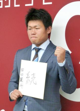 契約更改を終え、記者会見でポーズをとる巨人・田口=1日、東京都内の球団事務所