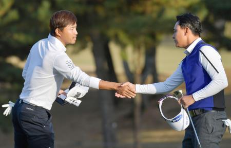 第2日、ホールアウトし、朴相賢(右)と握手する小平智。通算8アンダーで2位=東京よみうりCC