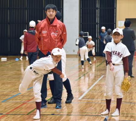 子どもたちに投球の指導をする岩隈久志投手=4日午後、熊本市