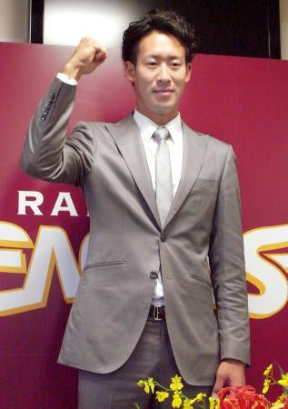 トレードで巨人から楽天に移籍し、入団会見でガッツポーズする小山=6日、仙台市の球団事務所