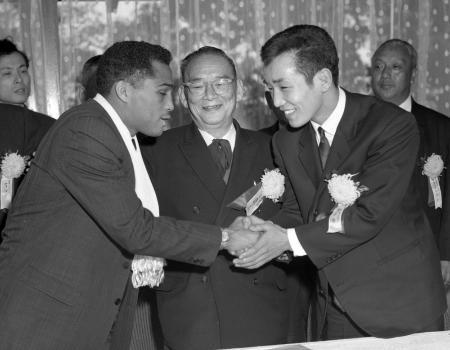 世界フェザー級タイトルマッチの調印後に握手をかわす関光徳(右)と、シュガー・ラモス=1964(昭和39)年2月12日、麻布プリンスホテル
