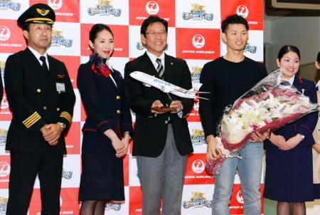 優勝旅行の出発を前に、日航職員から記念品を受け取った日本ハムの栗山監督(中央)。右隣は大野選手会長=12日、成田空港