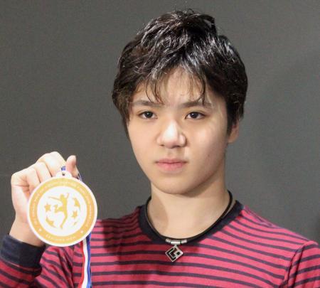 フィギュアスケートのGPファイナルから帰国し、獲得した銅メダルを掲げる宇野昌磨=13日午前、中部空港