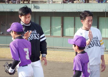野球教室で小学生とタッチを交わすソフトバンクの長谷川(左)と川島=18日、熊本市