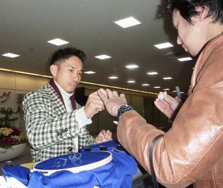 帰国し、ファンにサインするサッカー日本代表の長友佑都=23日、成田空港