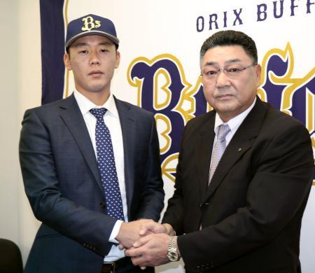 入団会見後、長村裕之球団本部長(右)と握手するオリックスの金田和之投手=26日、ほっともっとフィールド神戸