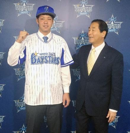 DeNAの入団記者会見でポーズをとる平良。右は高田繁ゼネラルマネジャー=6日、横浜市の球団事務所