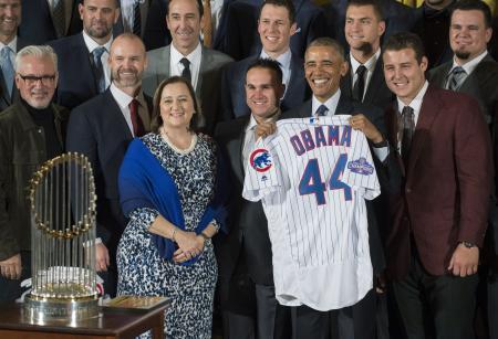 16日、贈呈されたユニホームを手に、ホワイトハウスを訪問した米大リーグ・カブスの選手らと記念撮影するオバマ大統領(UPI=共同)
