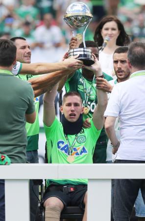 パルメイラスとの親善試合前、南米カップの優勝トロフィーを掲げるシャペコエンセのGKフォルマン=シャペコ(ロイター=共同)