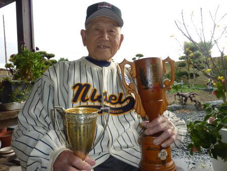 1944年の鶴嶺湖リーグで首位打者の入山正夫さん。首位打者トロフィーを持ち、米野球殿堂での日系野球展の記念ユニホームを着用(共同)