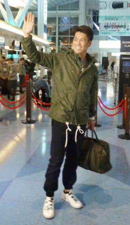 笑顔で手を振り、出発する米大リーグ、ドジャース・前田=26日夜、羽田空港