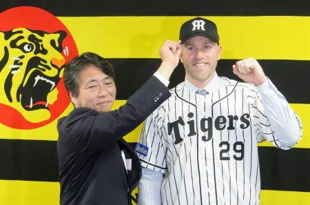 入団記者会見でポーズをとる、阪神の新外国人内野手キャンベル。左は高野栄一球団本部長=27日、兵庫県西宮市の球団事務所