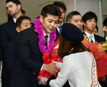 宮崎空港に到着し、歓迎の花束を受け取る広島・緒方監督=31日
