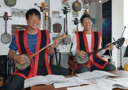 キャンプ初の休日で、沖縄伝統の弦楽器、三線の演奏に挑戦した中日の柳(左)と京田=沖縄県読谷村