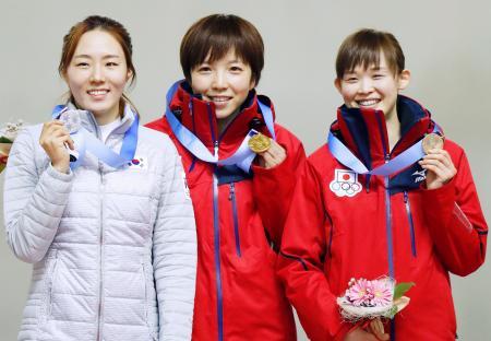 女子500メートルで獲得した金メダルを手に笑顔の小平奈緒(中央)と銅メダルの郷亜里砂(右)=明治北海道十勝オーバル