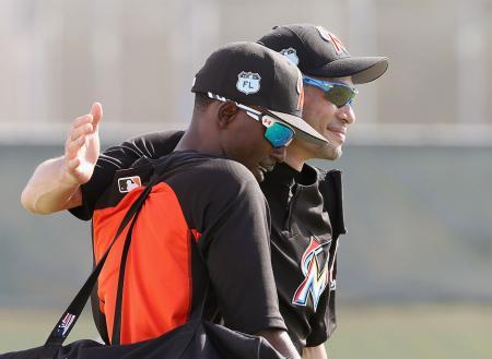 チームの全体練習に復帰し、ゴードン(左)と笑顔で抱き合うマーリンズのイチロー=ジュピター(共同)