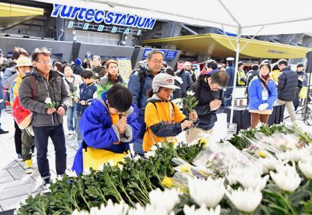 東日本大震災から6年を迎え、ユアテックスタジアム仙台に設置された献花台で手を合わせる人たち=11日午後、仙台市