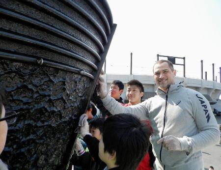 震災からの復興の象徴として貸し出されている1964年東京五輪の聖火台を地元の子どもたちと磨く五輪組織委の室伏広治さん=3月5日、宮城県石巻市
